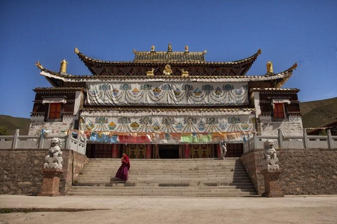 一名小和尚从金光闪耀的阿柔大寺正殿里走出.